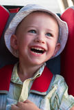 Un garçon riant s'asseyant dans une servocommande Image libre de droits