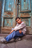 Un garçon s'asseyant au seuil images stock