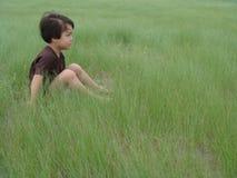 Un garçon s'asseyant dans une herbe verte grande Image libre de droits