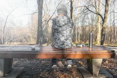Un garçon s'asseyant sur un banc en parc avec un thermos de boisson chaude image libre de droits