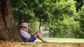 Un garçon s'assied sous le grand arbre de tilleul et lit un livre banque de vidéos