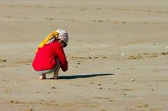 Un garçon s'assied sur la plage Photos libres de droits