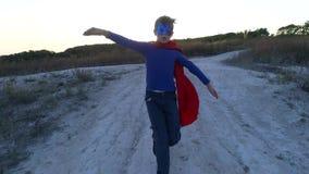 Un garçon s'est habillé avec un cap de Superman se tenant sur une montagne regardant le coucher du soleil banque de vidéos
