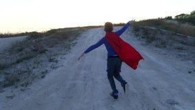 Un garçon s'est habillé avec un cap de Superman se tenant sur une montagne regardant le coucher du soleil clips vidéos