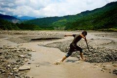 Un garçon sautent à travers une rivière Photos stock
