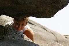 Un garçon scrutant entre les roches Images libres de droits