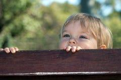 Un garçon se cachant derrière un banc Photographie stock libre de droits