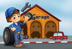Un garçon se tenant devant un garage Photographie stock libre de droits