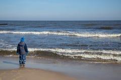 Un garçon se tient sur la plage observant la mer Image stock
