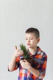 Un garçon se tient sur un fond blanc avec une usine le jour de la terre Images libres de droits
