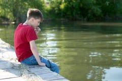 Un garçon songeur s'assied sur un pilier en bois, ayant abaissé ses pieds dans l'eau, et grignote une lame d'herbe images stock