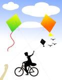 Un garçon sur le cycle célébrant la liberté avec des cerfs-volants Image libre de droits