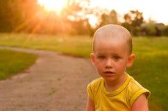 Un garçon sur le fond de coucher du soleil Images libres de droits