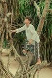 Un garçon sur un arbre dans le pantalon afghani Photos libres de droits