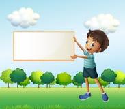 Un garçon tenant un conseil encadré vide Photos stock