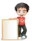 Un garçon tenant un conseil encadré vide Image stock