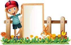 Un garçon tenant une bannière vide encadrée avec un lapin Images stock