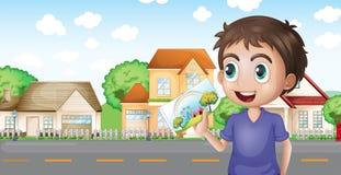 Un garçon tenant une photo devant les maisons près de la route Photos stock