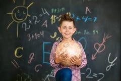 Un garçon tient un globe devant un conseil pédagogique photographie stock