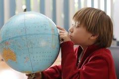 Un garçon touchant une carte de globe dans la classe et l'étude de géographie Photos libres de droits