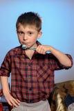 Un garçon triste dans des pyjamas n'est pas désireux pour se brosser les dents avant d'aller dormir sur un fond bleu photo libre de droits
