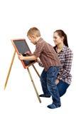 Un garçon, un femme et un tableau noir. Écriture Photos stock