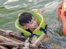 Un garçon utilisant un gilet de sauvetage pour nager sans risque et apprécier photographie stock libre de droits