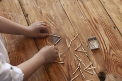 Un gar?on jouant avec des allumettes Le jeune gar?on joue des b?tons de match sur le fond en bois photographie stock