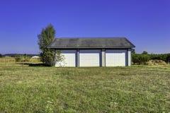 Un garage di tre automobili con il tetto di mattonelle Paesaggio della campagna Immagine Stock