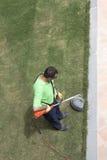 Un gardner avec un wacker d'herbe. Image stock