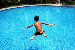 Un garçon saute dans l'eau Image libre de droits