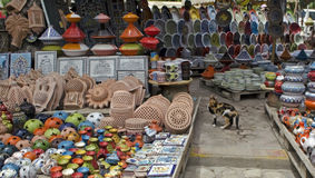Un gatto fra le merci multicoloured sul mercato africano Fotografia Stock