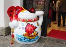 Un gatto giapponese fortunato o (di maneki-neko) davanti ad un negozio di ricordo in Hong Kong Fotografia Stock