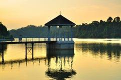 Un gazebo al bacino idrico sul tramonto Fotografia Stock