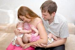Un gemello d'allattamento al seno delle due sorelle piccole Immagini Stock