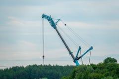 Un generatore eolico è eretto per mezzo di grande gru fotografie stock