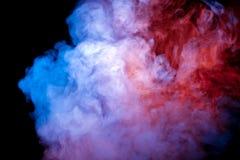 Un getto di fumo in ascesa ed esalato da un vape evapora alla luce al neon di un colore viola blu rosa contro un buio immagini stock