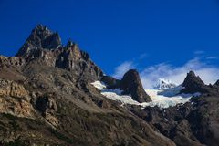 Un ghiacciaio sospeso, accoccolato sotto il granito alza alla cima di una delle montagne della valle francese in Torres Del Paine Immagine Stock