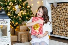 Un gilr moreno delante del piel-árbol y chimenea con las velas y los regalos Un sueño de la muchacha ` S Eve del Año Nuevo Navida fotos de archivo libres de regalías