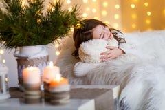 Un gilr moreno delante del piel-árbol y chimenea con las velas y los regalos Un sueño de la muchacha ` S Eve del Año Nuevo Navida fotografía de archivo
