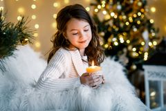 Un gilr moreno delante del piel-árbol y chimenea con las velas y los regalos Una muchacha que hace un deseo Muchos ornamentos y r fotografía de archivo