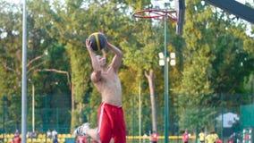 Un giocatore nello streetball fa una schiacciata video d archivio