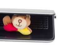 Un giocattolo sveglio della bambola che si nasconde sotto il computer portatile. Immagine Stock