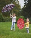 Un gioco delle due ragazze con l'ombrello Immagine Stock Libera da Diritti