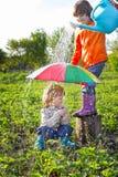 Un gioco di due fratelli in pioggia Fotografia Stock Libera da Diritti