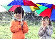 Un gioco di due fratelli in pioggia Fotografie Stock