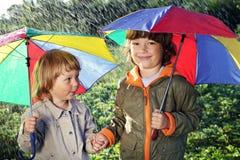 Un gioco di due fratelli in pioggia Fotografie Stock Libere da Diritti