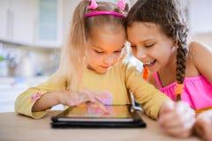 Un gioco di due sorelline su un PC della compressa Immagini Stock