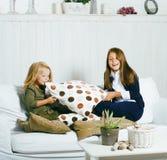 Un gioco interno sveglio di due sorelle a casa, sorridere poco felice fotografia stock libera da diritti