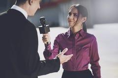 Un giornalista in un sorridere della camicia di Borgogna ascolta la risposta del ` s dell'uomo Fotografie Stock